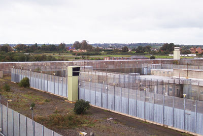 A photograph taken by Rab Kerr who was an Open University student in the Republican Wings of the H Blocks. It shows the Maze and Long Kesh Prison site in 2005. It is taken from a high vantage point and shows a watch tower in the middle of frame and two rows of tall security fences between prison buildings (H Blocks).